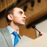 Man speaking from a lectern at a meeting