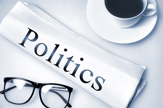 """illustration of the word """"politics"""" on a rolled up newspaper"""