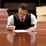 photo of an attorney sitting at table next to stacks of reports