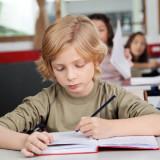 boy writing at a school desk