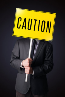 man holding a Caution sign