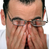 photo of tired man rubbing his eyes