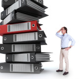 Information overload - man next to big stack of reports