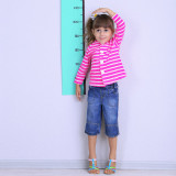 photo of a young girl measuring her height against a wall