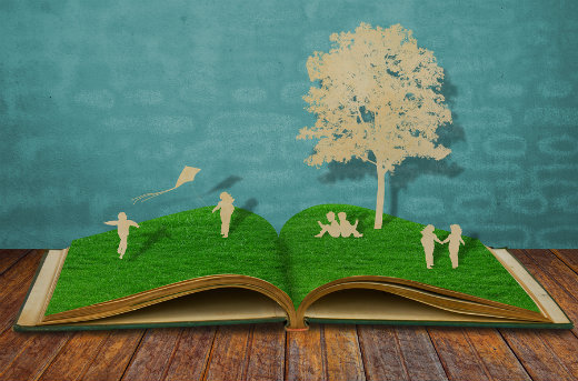 paper cut out of tree and children playing on grass covered book