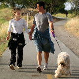 photo of a young couple walking their dog
