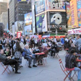 People enjoying new seating opportunities on Broadway in heart of Manhattan