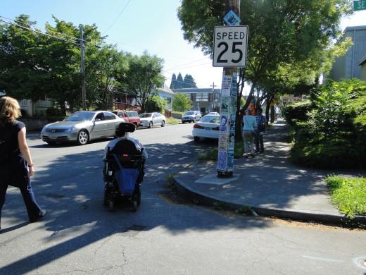 Motorized wheelchair user trying to cross street.