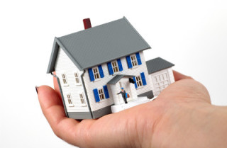 person holding a model of a house